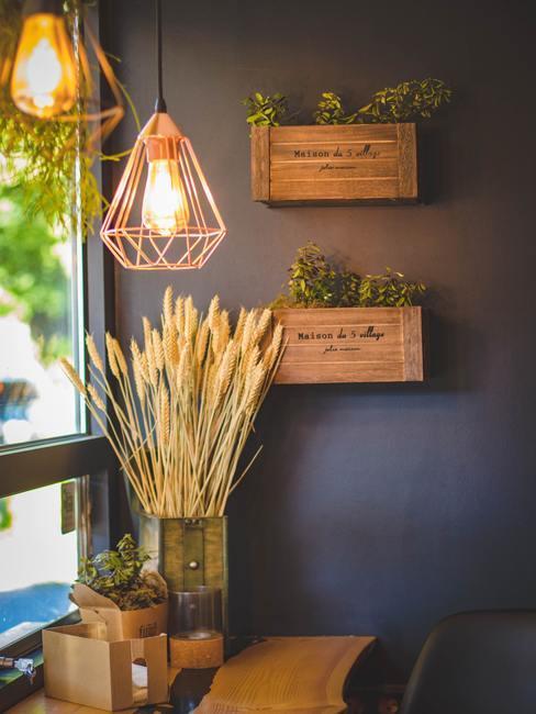 Houten kratjes aan de muur, bronzen hanglamp en stijlvolle lampen en graan in vaas