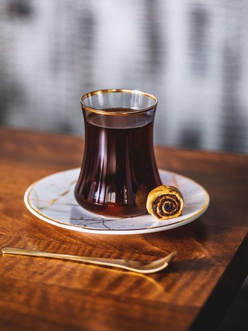 Thee in glas met gouden details op houten tafel voor het suikerfeest