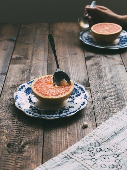 Delfts blauwe bordjes met halve sinaasappel op houten tafel