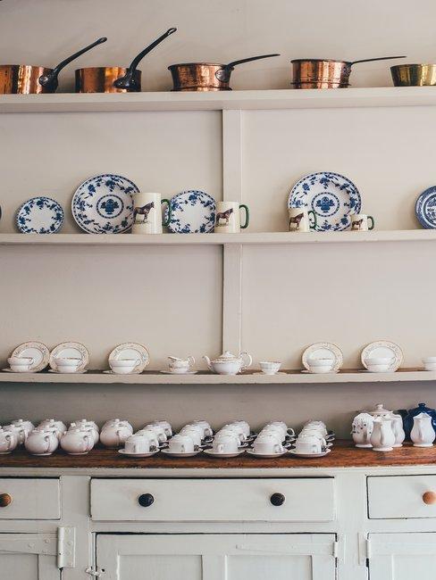 Witte houten kast met servies en pannen en delftsblauwe borden