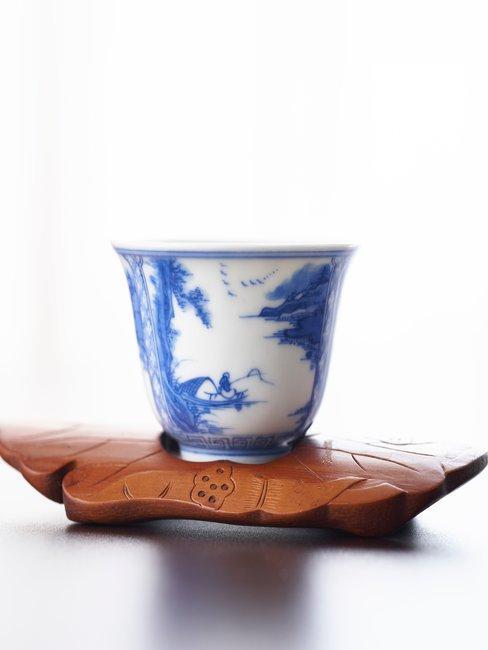 Delfts Blauw kopje op houten onderzetter met witte achtergrond
