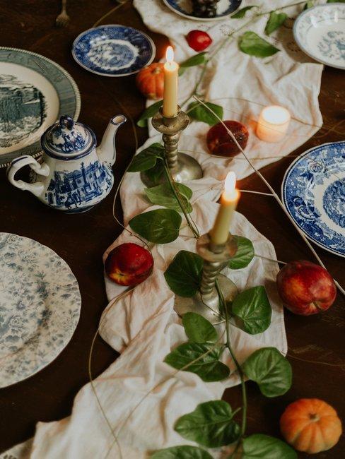 Houten tafel met witte tafellooper, kaarsen en delfts blauw servies