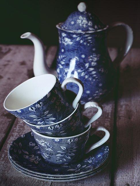 Delfts blauw servies theepot met kopjes op houten tafel