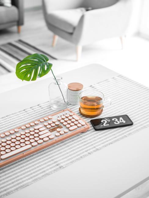 Tafel met roze toetsenbord glas thee en telefoon