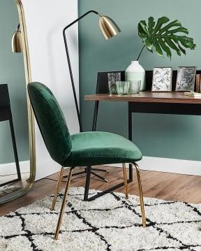 Groene wand met houten bureau en smaragdgroene stoel