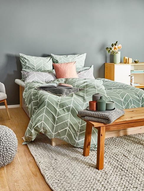 Grijsgroene muur met houten bed met beddengoed en accessoires in grijsgroen