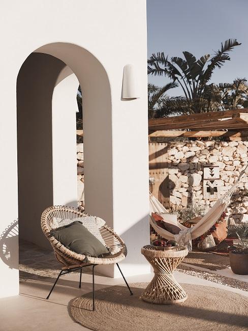 Mediterrane tuin met rotan meubels voor wit huis