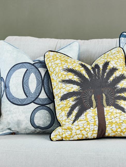Zbliżenie na szarą sofę z żółtą i niebieską poduszką