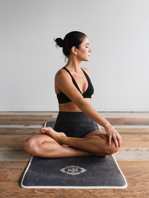 Kobieta w siadzie skrzyżnym i skręcie na macie do jogi