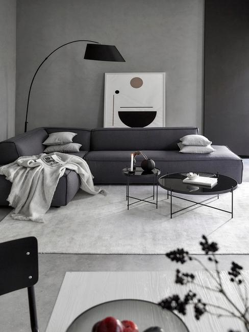Szary salon w stylu industrialny, ze czarną kanapą i lampą, białym dywaniem i elementami dekoracyjnymi