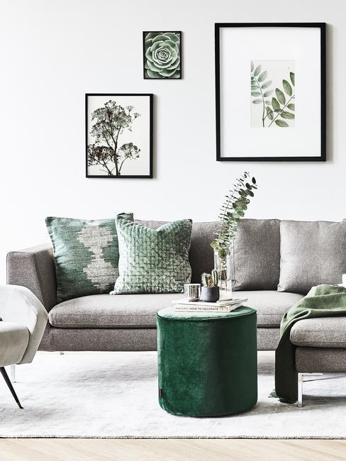 Szary salon z zielonymi akcentami w postaci puf, roślin, poduszek dekoracyjnych oraz obrazków na ścianie