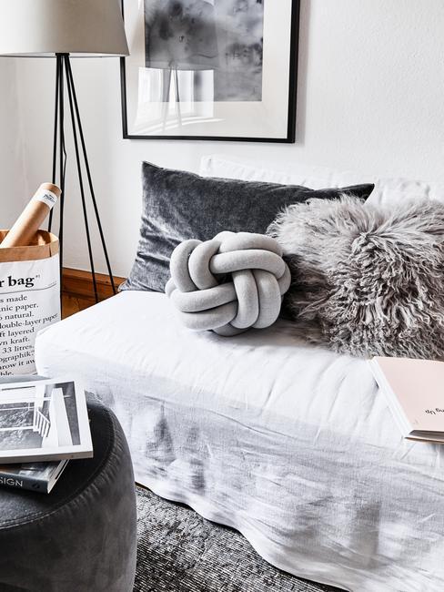 Salon cały w szarości z kanapą, lampą, obrazem, pufem oraz poduszkami dekoracyjnymi