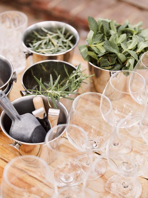 Kieliszki do wina oraz metalowe, srebrne doniczki z ziołami ustawione na drewnianym blacie