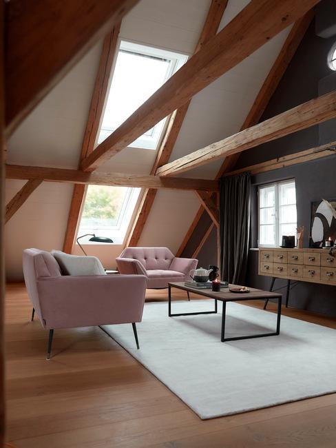 Salon na poddaszu w przestrzeni loftowej: dużo drewnianych elementów, różowe sofy i stolik kawowy