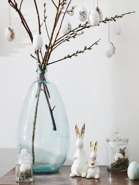 Wazon z galązkami wierzby z porcelanowymi dekoracjami w kształcie zajączków stojące na komodzie