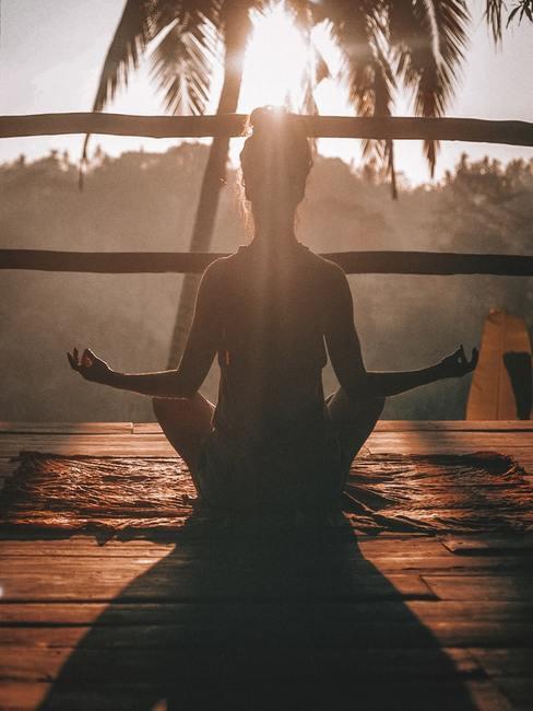 Dziewczyna medytująca na drewnianym balkonie w czasie urlopu