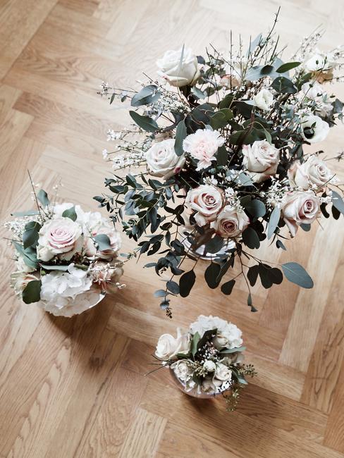 Trzy rodzaje bukietów kwiatów o różnej wielkości w wazonie na podłodze