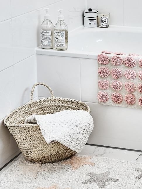 Fragment małej łazienki z wanną, koszem oraz tekstyliami