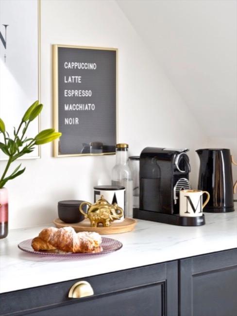 Zwarte keken met gouden accenten, marmeren keukenblad, zwarte ketel en wit serviesgoed