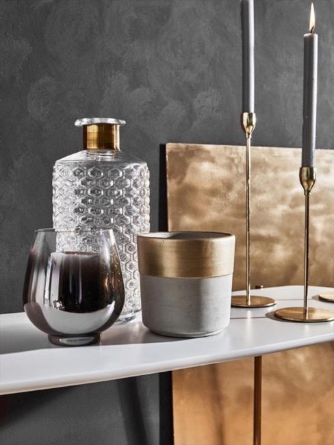 Grijze vaas met rand van geborsteld goudkleurig metaal naast glazen vazen en gouden kandelaar