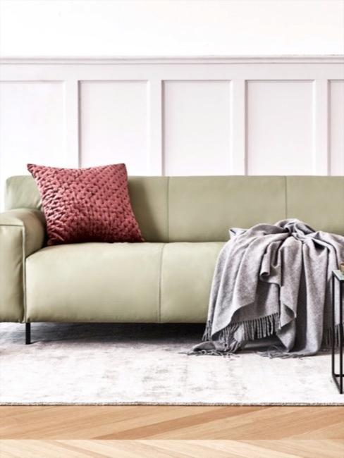 Zielona sofa z poduszką i pledem na tle białej ściany