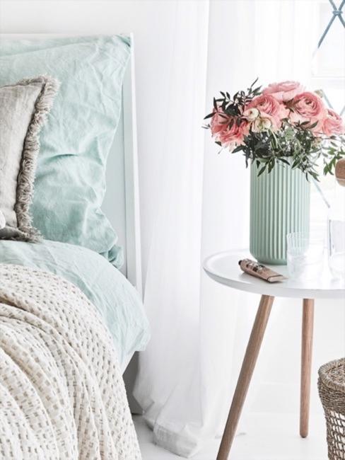 Woonkamer in pastelkleuren: grijze bank met pastelgroene kussens en dekens