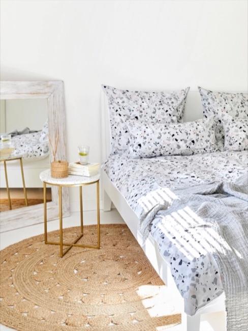 Białe łóżko z pościelą z motywem lastriko i biało-złotym stolikiem nocnym