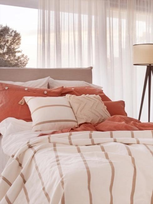 Sypialnia z lampą podłogową z plecionki wiedeńskiej obok łóżka boho w naturalnych odcieniach