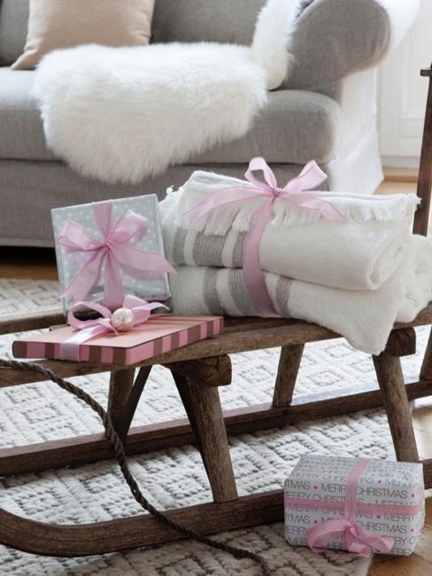 Décoration traîneau dans le salon avec plaides et cadeaux emballés