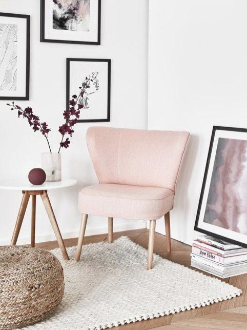 Sofá rosa en una esquina con cuadros sencillos enmarcados en negro sobre pared blanca
