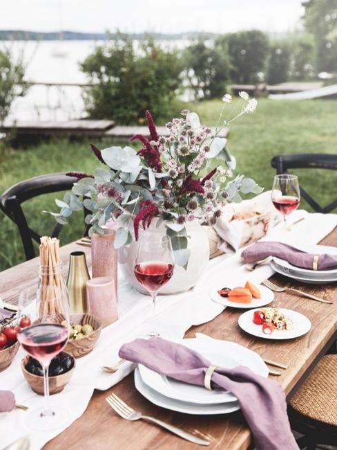 Stół w ogrodzie z zastawą i dekoracjami w odcieniach fioletu