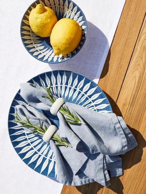Gros plan de la décoration de table d'été avec du romarin et des citrons posés sur les assiettes bleu-blanc