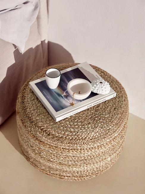 Rattanowy puf z książką i drobnymi dekoracjami