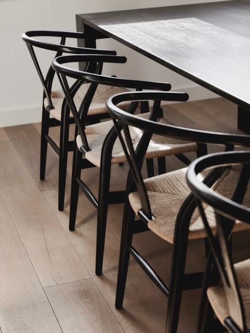 Zbliżenie na stół do jadalni i drewniane krzesła z siedziskiem z rattanu
