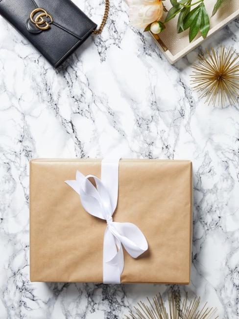 Gros plan d'un paquet cadeau sur une table en marbre avec des objets décoratifs