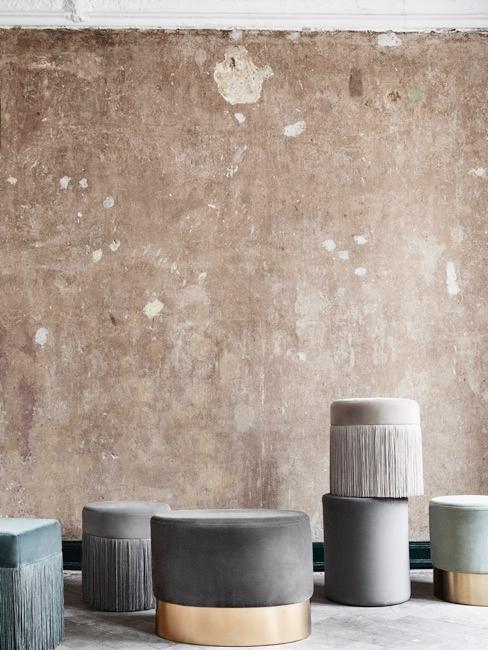 Pièce à murs gris bruts avec poufs de différentes tailles et couleurs