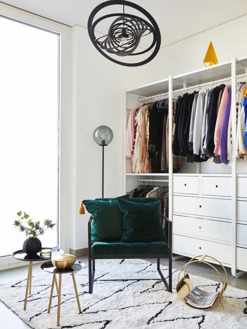Garderoba z częściowo otwartą szafą. Naśrodku krzesło z miękkimi poduszkami oraz biało-czarny dywan