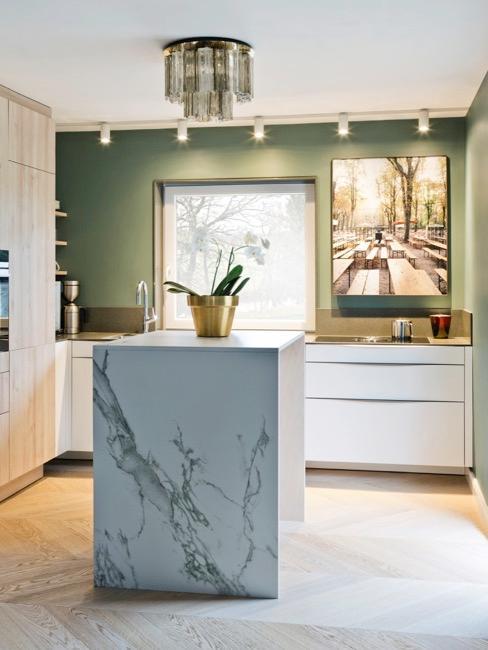 Cucina moderna con isola in marmo, elementi bianchi e dettagli oro
