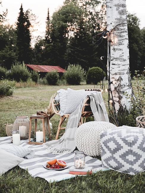 Picnic sul prato con lanterne da giardino, plaid e pouff chiari