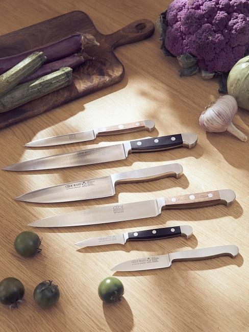 Mehrere Küchenmesser liegen nebeneinander auf Tisch
