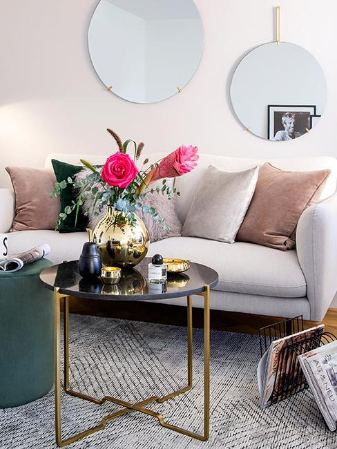 Nahaufnahme Couchtisch in gold und schwarzem Marmor vor grauer Skandi Couch