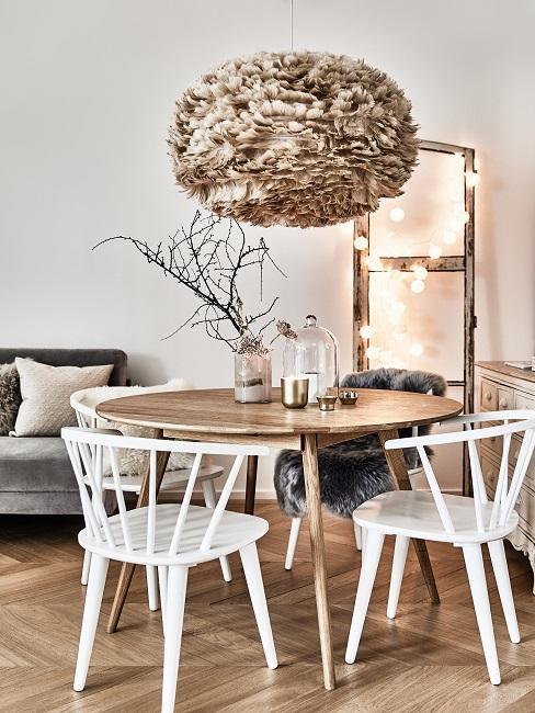 Eethoek in de woonkamer met witte stoelen en een hanglamp boven de tafel