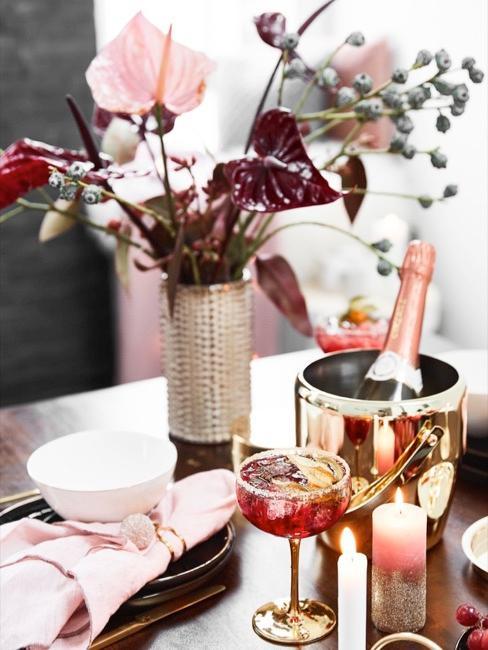 Goldener Sektkühler auf Esstisch mit rosa-roter Tischdeko