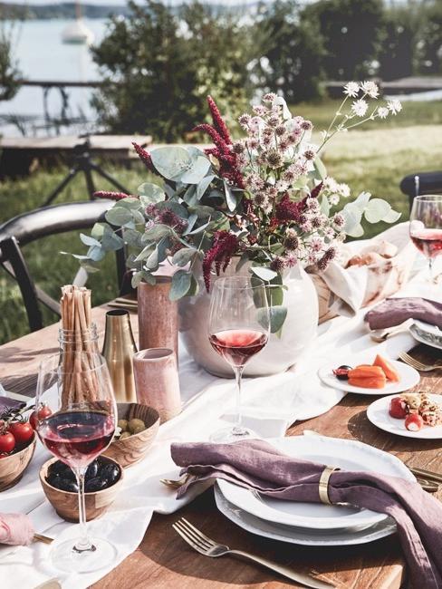 Butelka wina i kieliszki na stole w ogrodzie