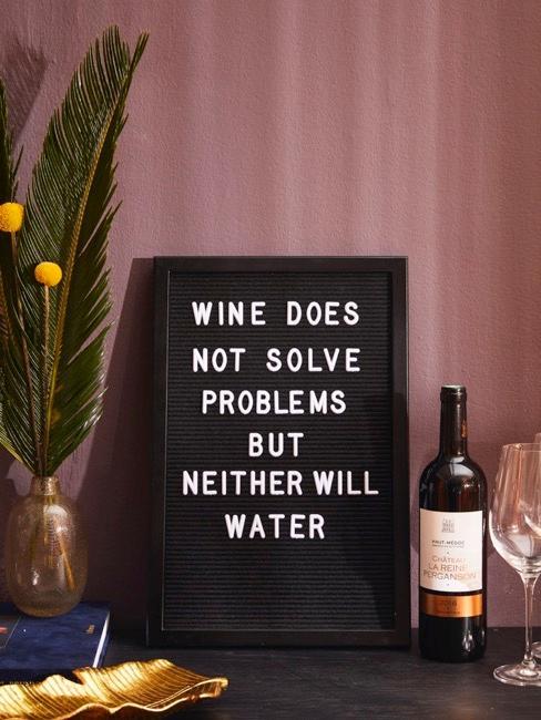 Tablica z napisem, obok butelka wina i kieliszek