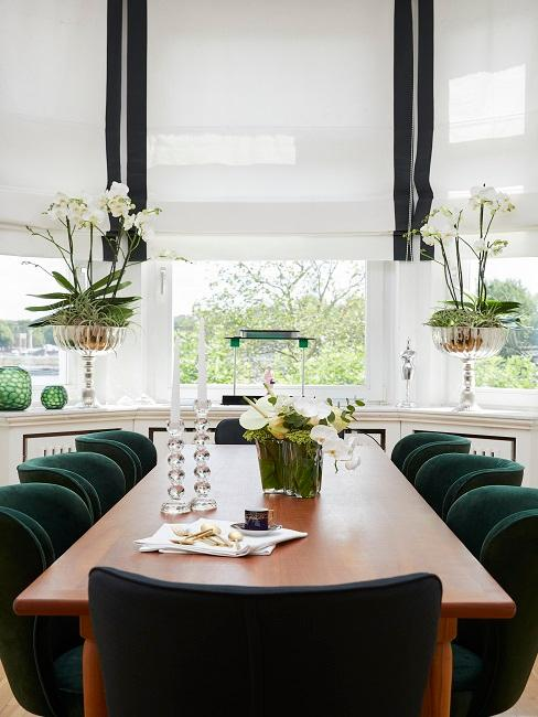 Dining table with green velvet chairs in front of a large window front