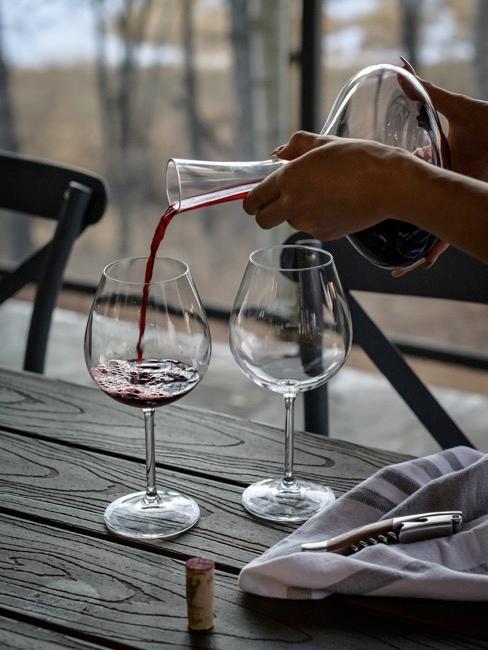 deux verres posés sur une table, deux mains de femme tiennent une carafe et versent du vin rouge