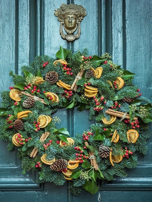 Door wreath with pine cones and dried oranges on a green door