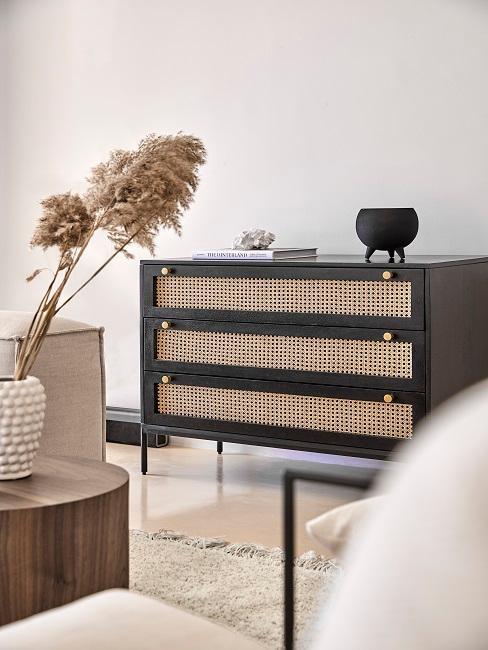 Ciemny kredens z plecionką wiedeńską w salonie z dużą ilością drewna i beżowych odcieni