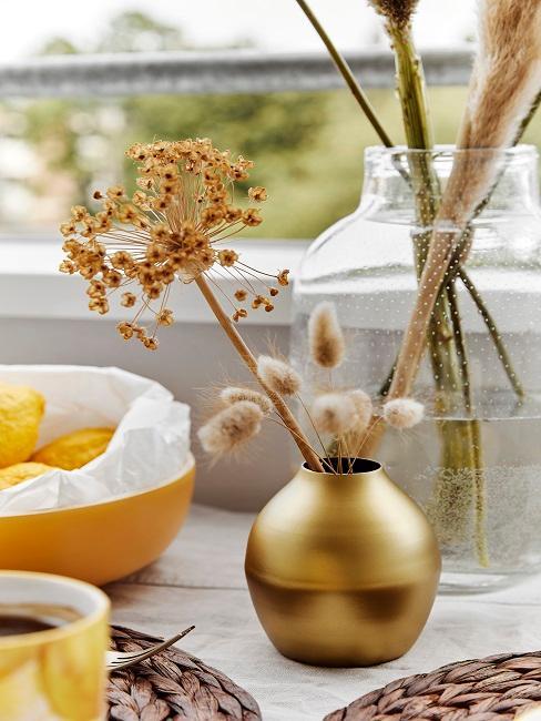 Kleine goldene Vase neben weiteren Dekoelementen